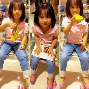 Little fashionista trying on the pink and yellow shoes.