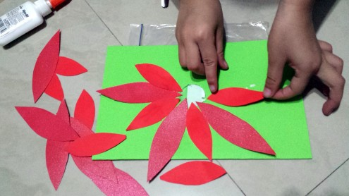 Step 5: Cut a hole in the middle of the front side of the card and then glue the petals around the hole